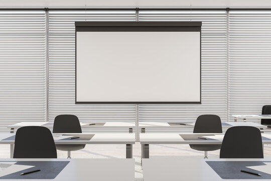 Blank white screen in the center of modern seminar room with rows of tables and chairs. Mockup. 3D rendering