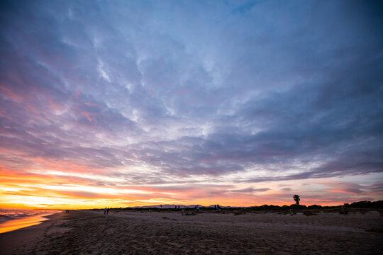 Atardecer desde la playa de Barcelona con cielo nublado