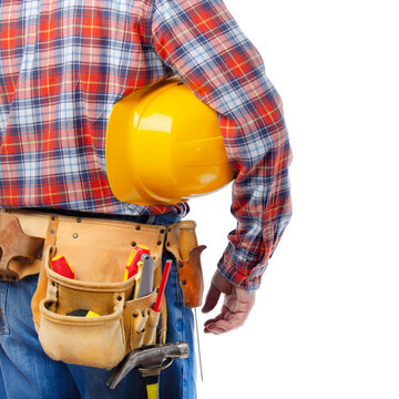 Middle aged caucasian contractor with tool belt holds yellow hard hat under his hand on white background