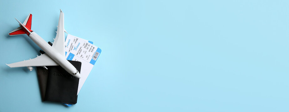 Toy airplane and passports with tickets on light blue background, flat lay. Space for text