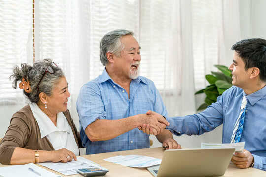 Businessman Shaking Hands With Senior Man In House