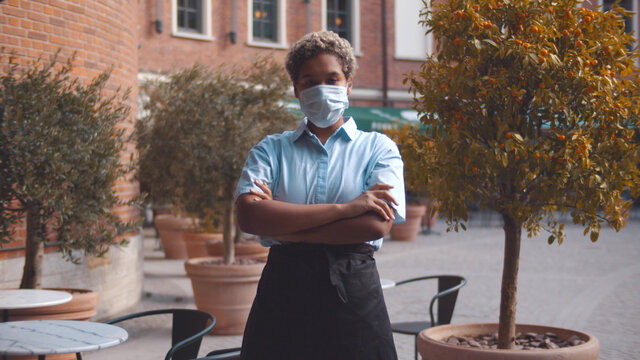 Portrait of afro-american waitress wearing face mask standing on cafe terrace