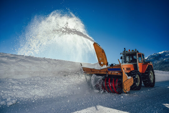 A snowplow truck removing snow from a winding rural road on sunny winter day.