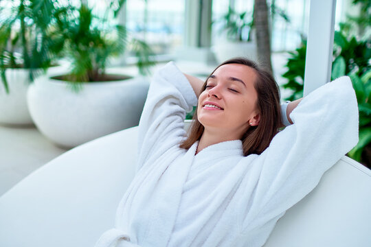 Serene calm woman wearing white bathrobe with closed eyes and hands behind head enjoying relaxing time and feeling good at a wellness spa resort. Easy lifestyle and satisfaction