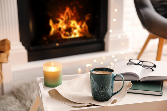 Cup of coffee, burning candle and books on tray near fireplace indoors. Cozy atmosphere