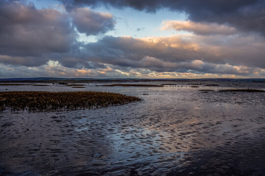 Evening clouds reflect on mud and water in the Skern area of Northam Burrows, near Appledore, North Devon.