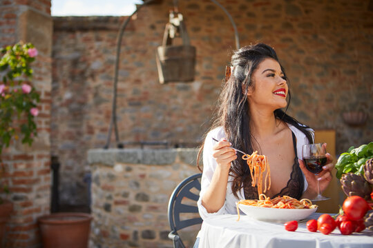country life. An Italian woman eats dinner and pasta in her home garden