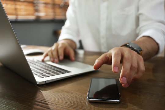 Freelancer taking smartphone while working on laptop at table indoors, closeup