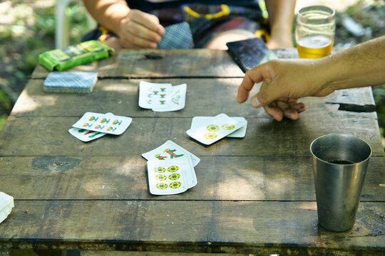 Personas Latinoamericanas jugando a las cartas de truco al aire libre. Familia jugando