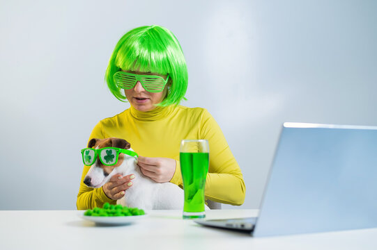 A young woman in a green wig and cheerful glasses drinks beer and bites glazed nuts. A girl sits with a dog at a table and celebrates st patrick's day online chatting with friends on a laptop.