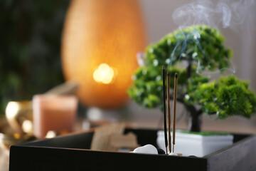 Miniature zen garden with smoldering incense sticks, closeup. Space for text