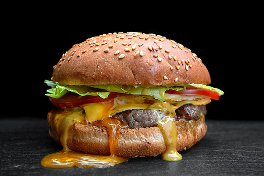 Burger, cheeseburger, hamburger with meat cutlet, cheese, lettuce and tomato, on a black background