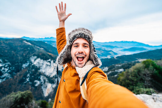 Happy man taking a selfie climbing mountains - Smiling hiker hiking hill - People, technology and sport concept