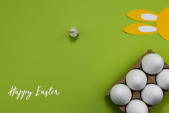 Easter image with a small white chick on a green background with bunny ears and white eggs in a carton.