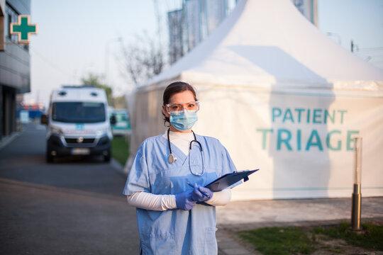 Portrait of serious female key front line worker in blue PPE uniform