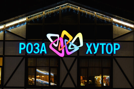 Sochi, Russia - January 4, 2018: Colorful neon illuminated Rosa Khutor ski mountain resort sign on building exterior. Rosa Khutor logo background.