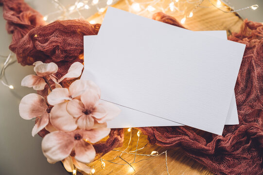 Top view blank white card and flowers on wooden plate or board on grey table background. Modern minimalist template.