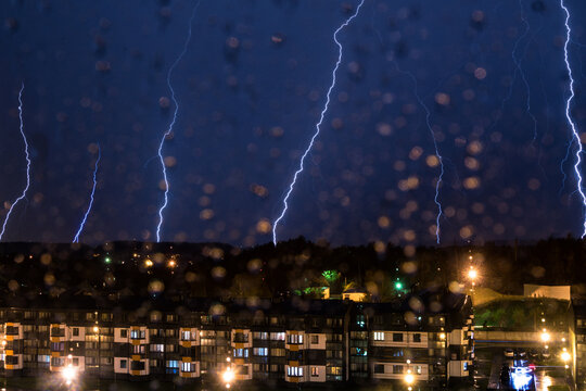 Thunderstorm over city in the night with many lightning bolts