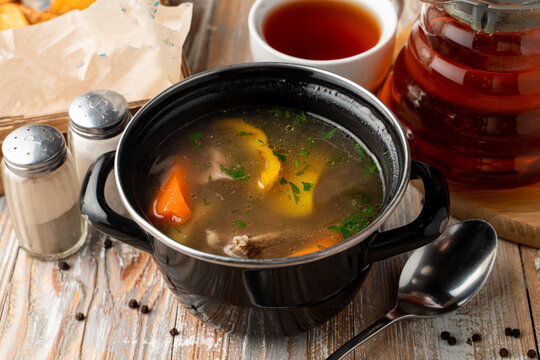 Spicy and warm autumn soup on meat broth, served in rustic pot on a wooden table
