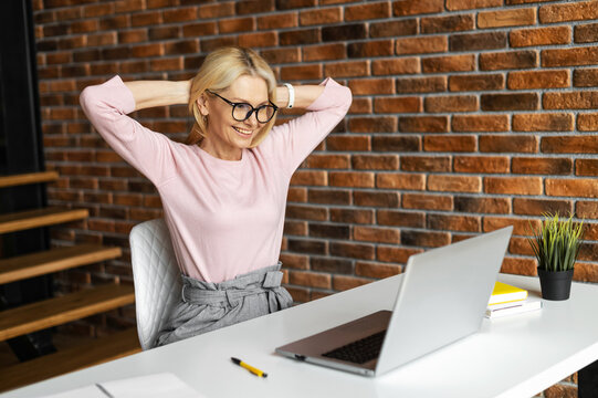 Mature mid-age businesswoman sitting at the desk, looking at the laptop and smiling, excited, satisfied and relaxed, enjoying the end of a workday, relaxed posture hands behind head. Well done concept