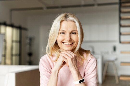 Portrait of a charming elegant mature middle-aged businesswoman with hands on a chin smiling at the camera, sitting in the modern house, wearing pink sweater. The view while the video-calling concept