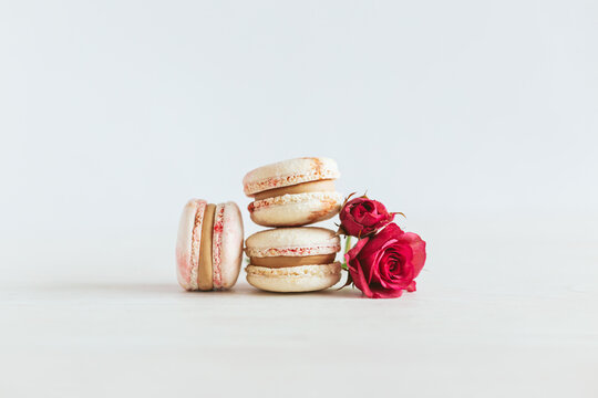 Tasty french macaroons with pink roses on a white wooden background.