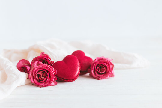 Heart-shaped macaroons with pink rose on a white wooden background. Concept for Valentine's Day.