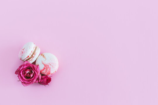 Tasty french macaroons with pink roses on a pink pastel background.