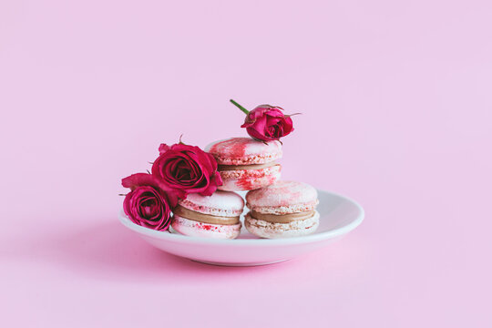 Tasty french macaroons with pink roses on a white plate. Pink pastel background.
