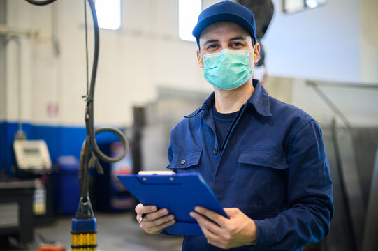 Portrait of a worker in an industrial plant wearing a mask, coronavirus concept, holding a clipboard
