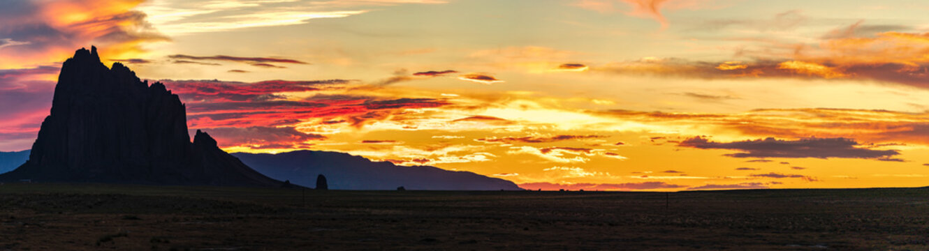 Epic panorama of New Mexico sunset with Shiprock as a silhouette in the background.