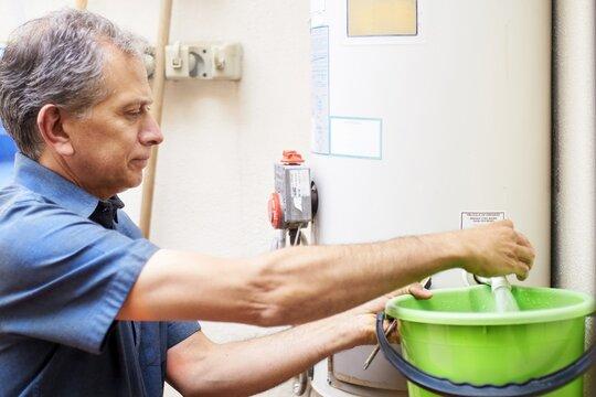 Man checking water boiler at vacational rental property