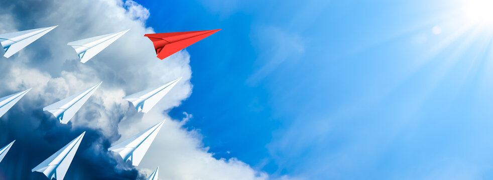 Red Paper Airplane Leading Fleet Of Small White Planes Away From Approaching Storm Toward Blue Sky And Sun - Leadership Concept