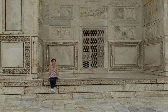 Woman sitting on a wall at the Taj Mahal, Agar, Uttar Pradesh, India