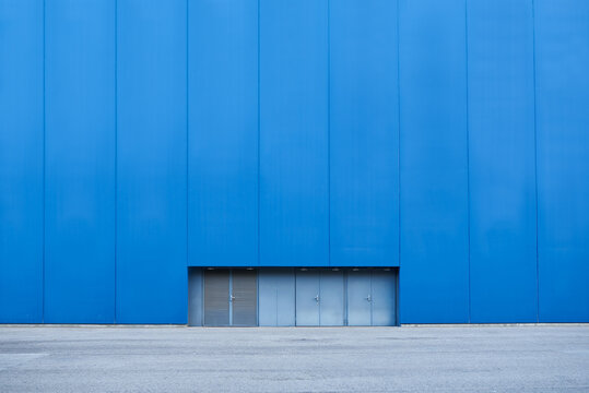 Bright blue wall of industrial building with windows in basement