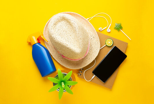 Summer holiday compozition with straw hat, pineapple drink glass, smartphone, notebook, yellow background, sun care cream copy space, flat lay.