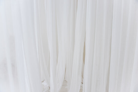 Background texture of white, airy stripes of chiffon fabric, tulle. Neutral colors. Minimalist interior decoration. Scandinavian style. Copy space