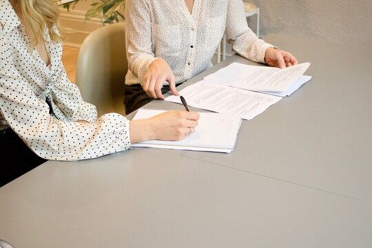 Person writing on a document,someone else is arranging the documents