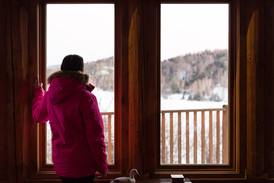 Woman looks at snowy landscape through window of ski chalet in m