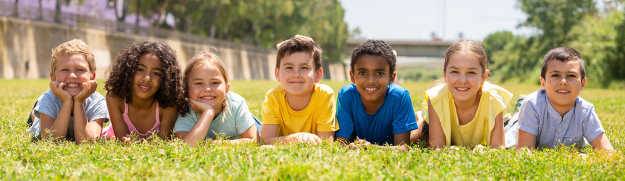 Group of school children resting on grass and smiling together in park