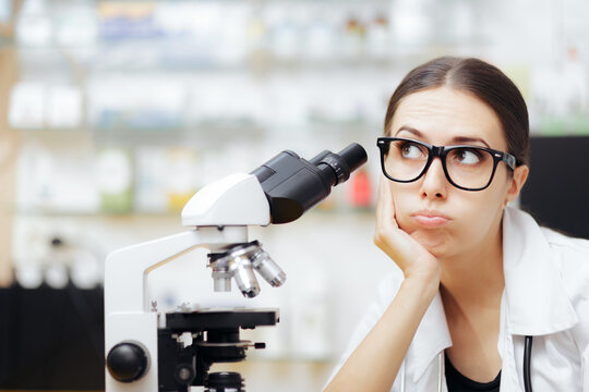 Unhappy Scientist Looking through a Microscope in a Laboratory