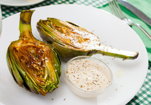 Vegetarian appetizer of roasted halved artichoke served with kosher salt and savory dip sauce ..