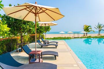 Fototapeta Umbrella and chair around outdoor swimming pool in hotel resort