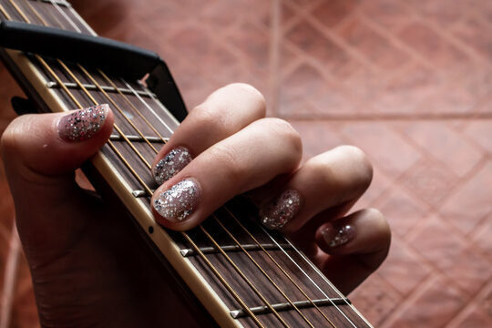A woman with glitter nail polish plays a G Major chord on an accoustic guitar, fitted with a capo, February 2021 during COVID-19 lockdowns.