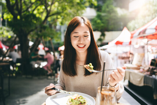 Young adult asian woman eat lunch food at restaurant outdoor on weekend day