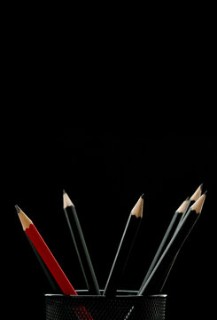 One red pencil in a holder together with other black pencils