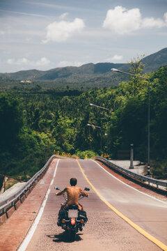 Senior motorcyclist riding his bike in tropics