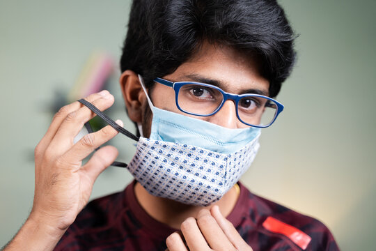 Young man wearing double or two face mask to protect from coronavirus or covid-19 outbreak - concept of safety, healthcare, medical and hygiene
