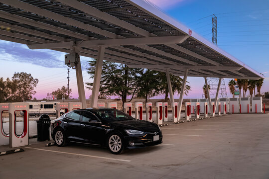 Firebaugh, USA - January 21, 2021: Black electric luxury Tesla Model S 75D car at a 250 kW Supercharger on California Highway 5 at sunset