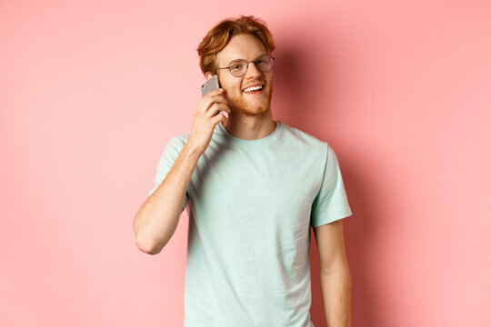 Handsomy hipster guy with red hair and beard talking on mobile phone, calling someone and looking happy, standing over pink background
